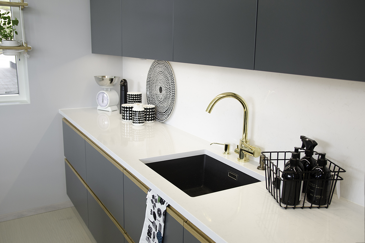 White-grey kitchen with a golden faucet